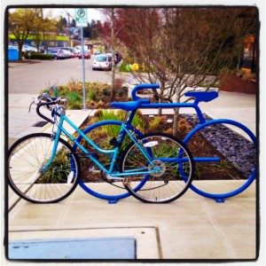Turquoise blue bike against electric blue bike rack shaped like a bicycle