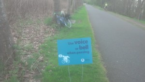 "Sign on Burke-Gilman Trail bike path, ""Use voice or bell when passing"""