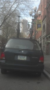 Share the Road license plate personalized with WA BIKES, 2 bikes on roof rack, parked in Pioneer Square, Seattle