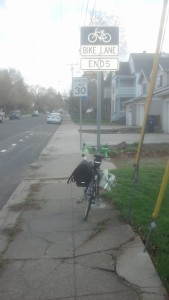 Bike Lane Ends sign, bike loaded with bags leaning against pole