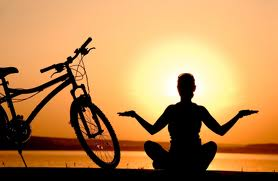 Peaceful sunset and bike with person sitting in lotus pose