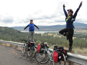 Two women doing yoga along a guide rail on their bike tour -- not something you see every day.