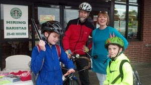 Thurston County Bike to Work Energizer Station, 2014. Duncan Green (left, standing with Barb Chamberlain)) has organized Thurston County's Bicycle Commuter Challenge for years. The boy at left gets ready to put on his reflective slap band with great enthusiasm.