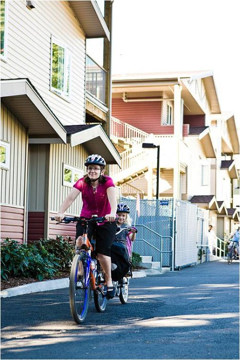 Mary Anderson and Izzy roll in Bellingham. Mother and daughter on bike with trail-a-bike behind.