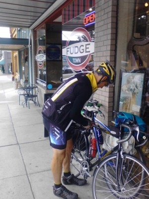 Rider with two bicycles and panniers outside Snohomish Bakery Creations, Snohomish, WA