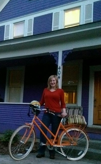 Young white blonde woman wearing red sweater with orange bicycle in front of a purple house with white trim