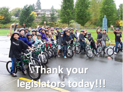 Kids on bikes waving. Text: Thank your legislators today!!! (Photo property of Washington Bikes, WAbikes.org)