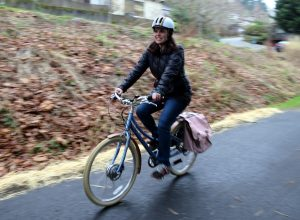 woman rides bike with pink fenders