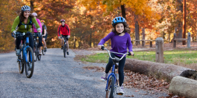 Girl and mom biking on a trail during the fall