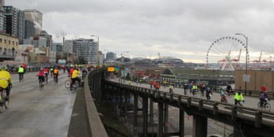 People on bikes ride across the now-defunct SR 99 tunnel with the Seattle Ferris Wheel in the background